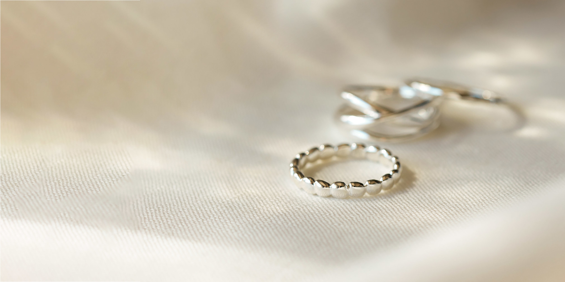 Plain silver rings on white cloth backdrop