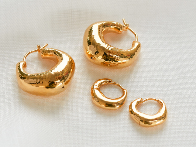 A selection of textured gold rings on a white background