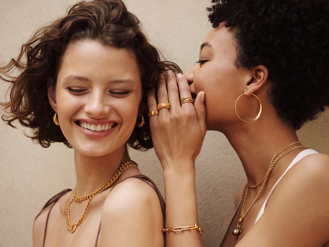 A model whispering to another, wearing a variety of gold pieces.