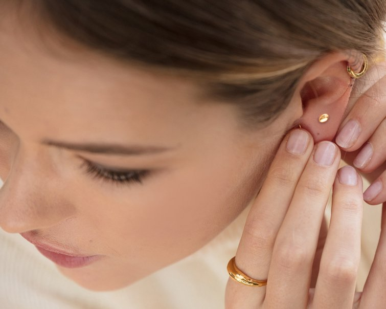 Model adding a new earring to their piercing stack.
