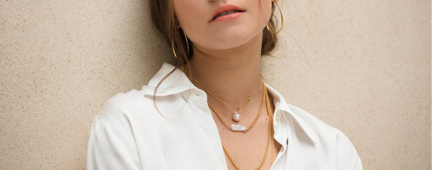 A model styling the Monica Vinader Biwa Pearl Necklace, layered with a Nura Baroque Pearl on gold chains.
