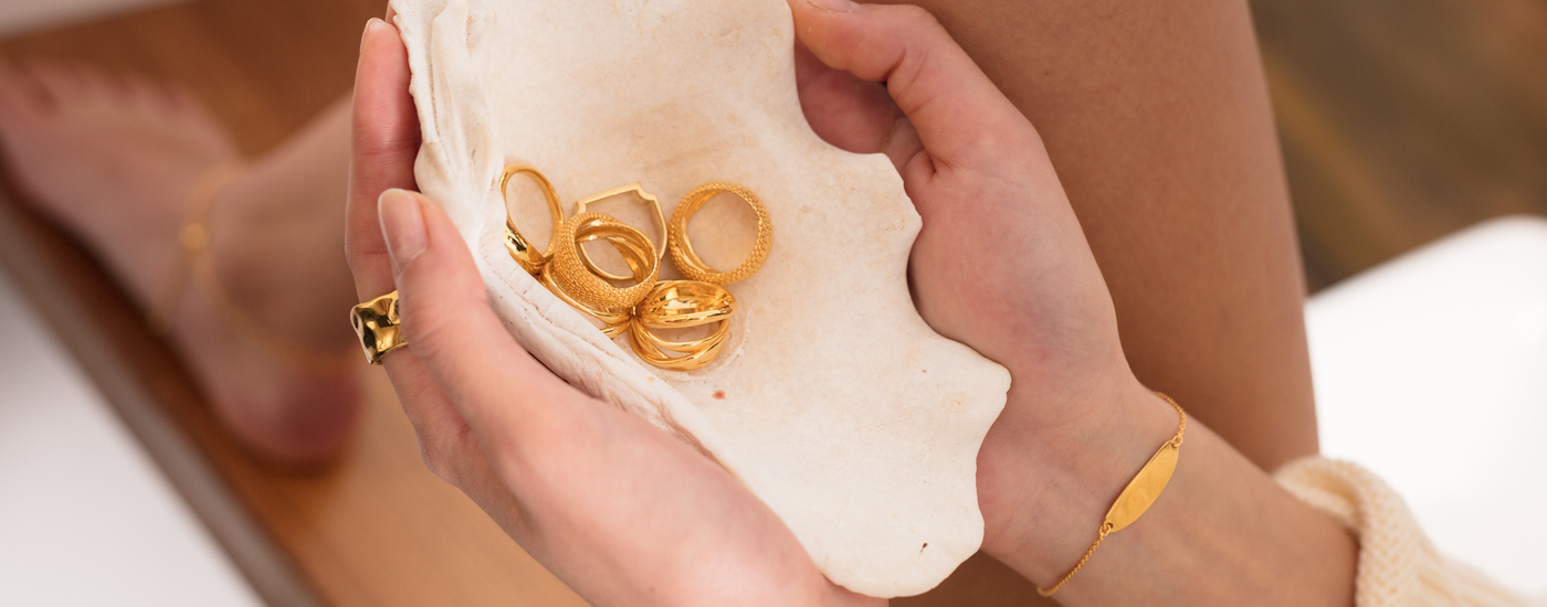 A selection of gold rings in a white shell, held by a model.