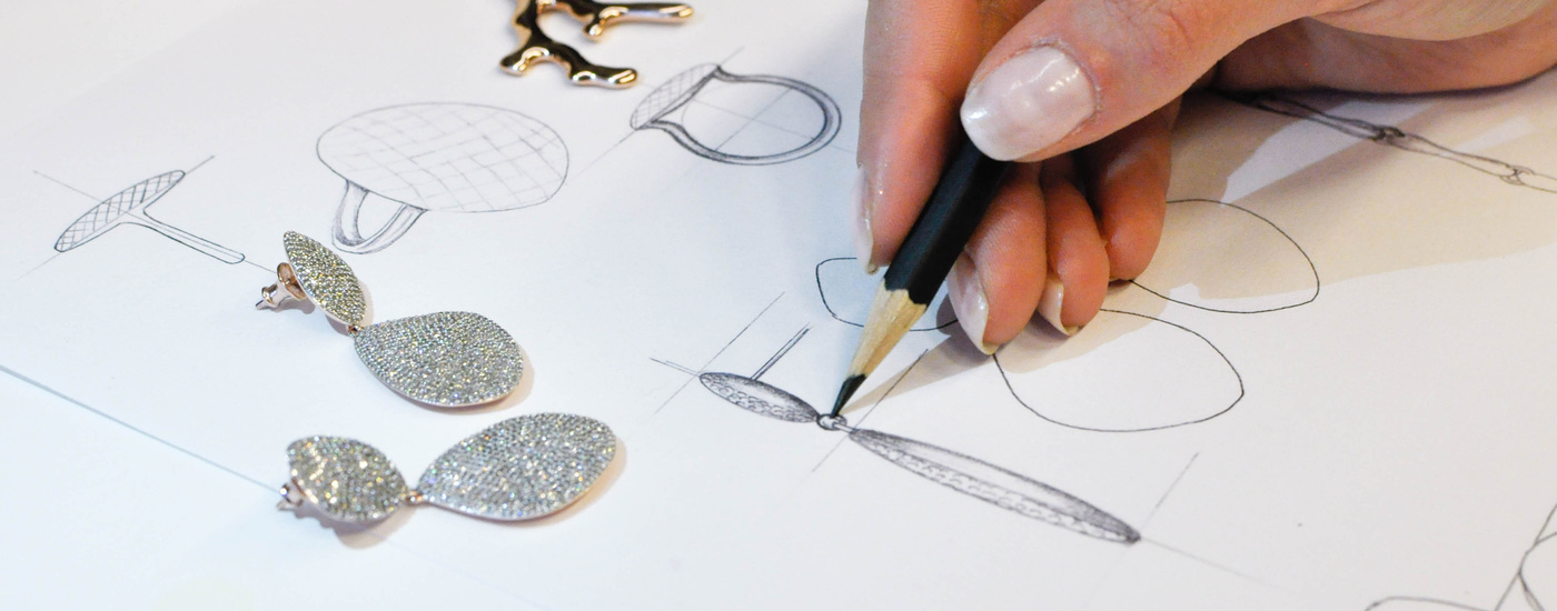 An artist drawing sketches of the Monica Vinader Teardrop Cocktail Earrings