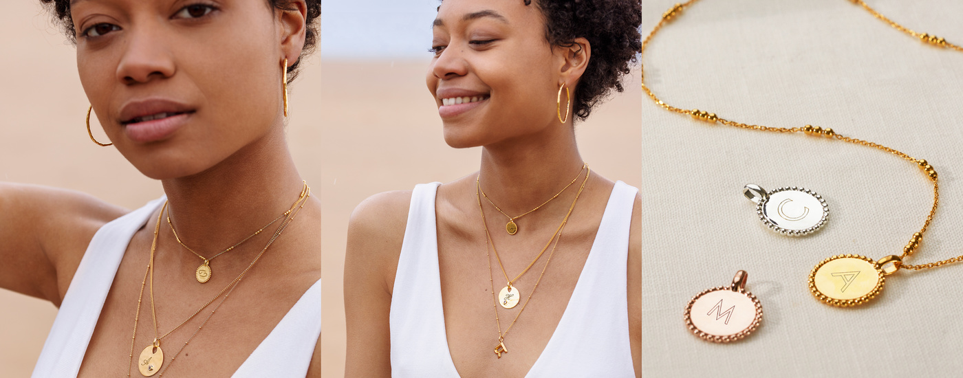 A model styling a selection of gold pendant charms