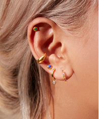 Close up a model's ear wearing gold earrings featuring a mix of semi-precious gemstones.