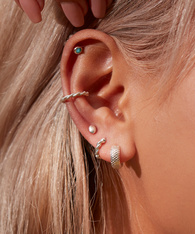 Close up of a model's ear, wearing a mix of silver earrings