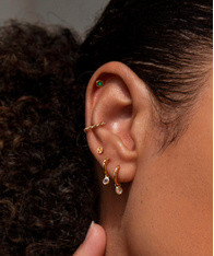 Close up of a model's ear, wearing a mix of gold earrings including some gemstone huggies.