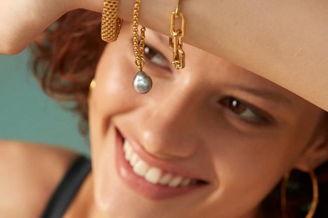 Model wearing a stack of gold vermeil bracelets