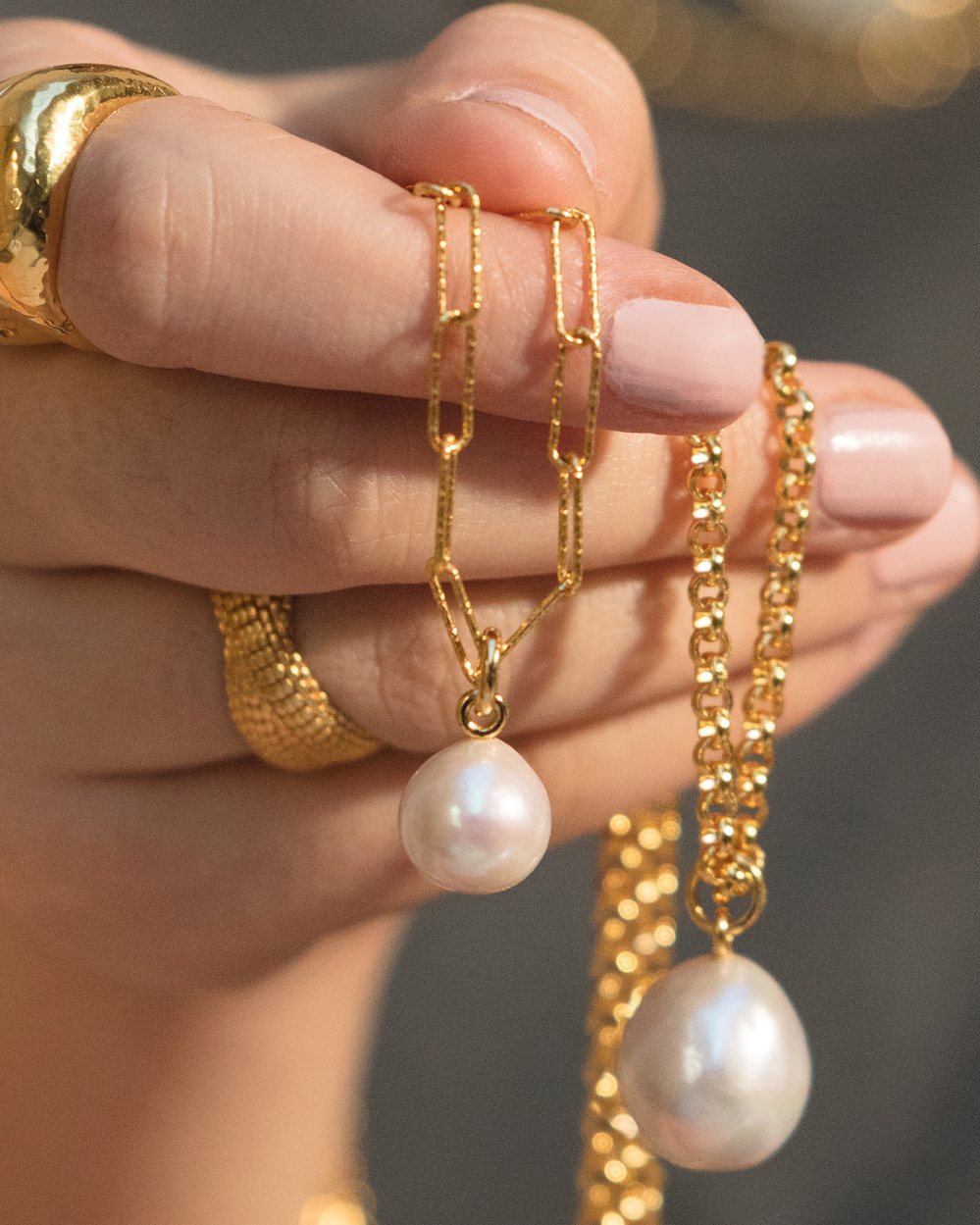 Close up of a model's hand holding a few Nura Baroque Pearls, styled on a variety of gold chains.