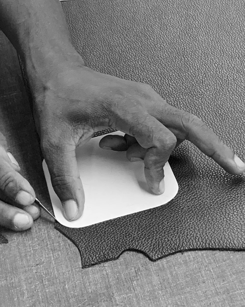 A black & white image of a master craftsman cutting leather to size.
