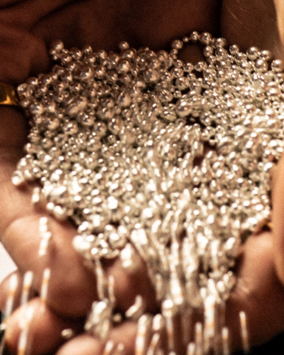 Close up of silver beads pouring from someone's hands onto a table