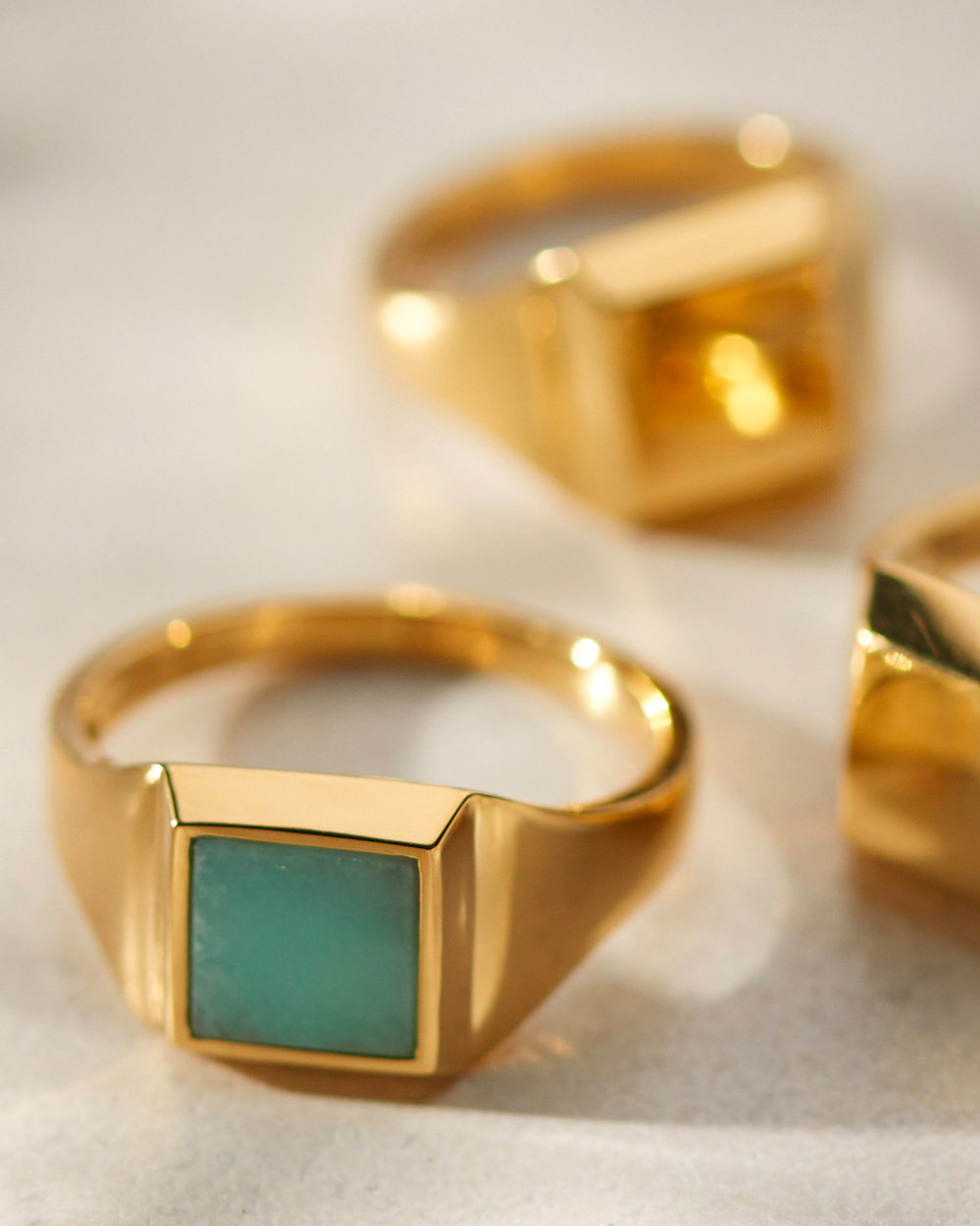 Three gold Monica Vinader Signet Rings, one with Amazonite embedded.