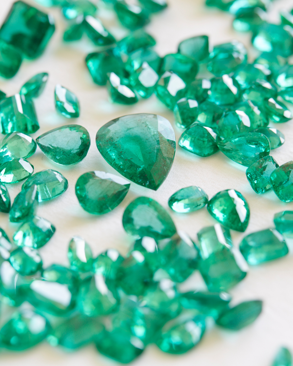 A close up of emerald stones laid out on a table.