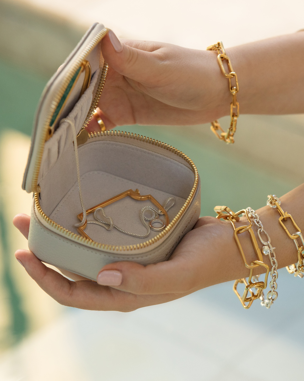 Model holding open a Monica Vinader jewellery box, wearing a mix of gold and silver pieces